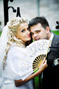 Happy bride and groom with fan near fence Stock Photography