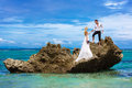 Happy bride and groom having fun on a tropical beach under the p Royalty Free Stock Photo