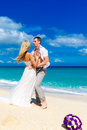 Happy bride and groom having fun on a tropical beach wedding bo bouquet in the foreground Royalty Free Stock Photography