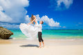 Happy bride and groom having fun on a tropical beach wedding an honeymoon the island Royalty Free Stock Photos