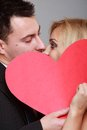 Happy bride and groom kissing behind red heart wedding day blonde a gray background Stock Images