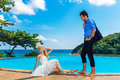 Happy bride and groom poolside infinity tropical sea in the bac background Stock Photo