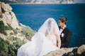 Happy bride and groom posing on the ocean background