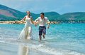 Happy Bride and groom running on a beautiful tropical beach Royalty Free Stock Photo