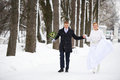 Happy bride and groom running in winter park on wedding day Stock Photo