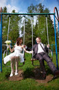 Happy bride and groom on swing Royalty Free Stock Images