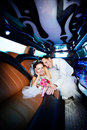 Happy bride and groom in wedding limo Royalty Free Stock Photography
