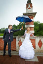 Happy bride and groom at wedding under an umbrella Royalty Free Stock Images