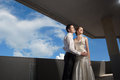 Happy bride and groom at the wedding walk in front of blue sky in city Stock Images