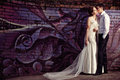 Happy bride and groom at the wedding walk in front of colorful wall Royalty Free Stock Image