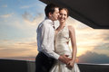 Happy bride and groom at the wedding walk in front of sunset in city Royalty Free Stock Photos