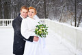 Happy bride and groom on winter park in snowy weather Stock Photo