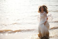 Happy bride lace dress running near waterline Stock Photo