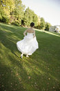 Happy bride running in park full length rear view of a smiling Royalty Free Stock Photos