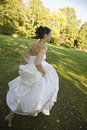 Happy bride running in park full length side view of a smiling Stock Photo
