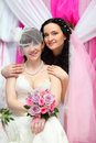 Happy bride stands behind other bride Stock Images