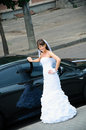 Happy bride in white dress standing near wedding car a Royalty Free Stock Photo