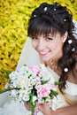 Happy bride with white wedding bouquet on flowers background Royalty Free Stock Photo