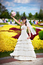 Happy bride with white wedding bouquet on flowers bed background Royalty Free Stock Photography