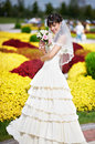 Happy bride with white wedding bouquet on flowers bed background Royalty Free Stock Photo