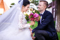Happy bridegroom looking at beautiful bride holding bouquet outdoors Royalty Free Stock Photo