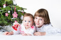 Happy brother and baby sister playing together under a christmas tree Royalty Free Stock Images