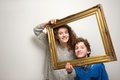 Happy brother and sister holding picture frame Royalty Free Stock Photo