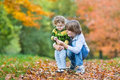 Happy brother and toddler sister in autumn park Royalty Free Stock Photo