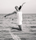 Happy brunette girl jumping over the sea stylized as retro photo black and white Royalty Free Stock Images