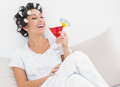 Happy brunette in hair curlers sitting on her bed holding a cock cocktail bedroom at home Stock Images