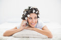 Happy brunette in hair rollers lying on her bed making a phone c call bedroom at home Royalty Free Stock Photos