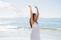 Happy brunette in white sun dress holding sarong on the beach Stock Photo