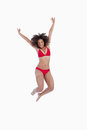 Happy brunette woman jumping while raising her arms Stock Photo