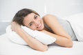 Happy brunette woman lying on her bed in the bedroom smiling cheerfully at camera Royalty Free Stock Photos