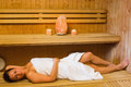 Happy brunette woman lying in a sauna wearing white towel Stock Photography
