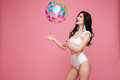 Happy brunette woman wearing swimsuit and playing with beach ball Royalty Free Stock Photo
