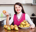 Happy brunnette girl with pears in home kitchen Royalty Free Stock Image