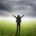 Happy business man in green fields and rainclouds on bad day Royalty Free Stock Images