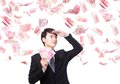 Happy business man hold china money renminbi under a rain isolated over a white background asian model Royalty Free Stock Image
