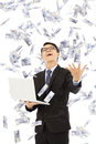 Happy business man holding a laptop and catching money with rain Royalty Free Stock Photos