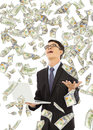 Happy business man holding a laptop with money rain Royalty Free Stock Photo