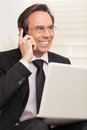 Happy business man speaking on cellphone while at stairs handsome using a laptop and the Royalty Free Stock Photo