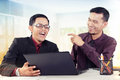Happy business partners laugh two young asian laughing on a discussion at their workplace Stock Image