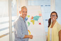 Happy business people with world map in meeting room Royalty Free Stock Photo