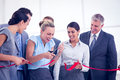 Happy business team cutting red ribbon Royalty Free Stock Photo