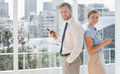 Happy business team standing back to back and texting by large windows Royalty Free Stock Image