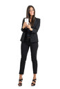 Happy business woman in black suit taking photo with cellphone full body length portrait isolated over white studio background Royalty Free Stock Images