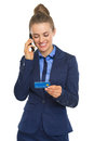 Happy business woman with credit card talking cell phone Royalty Free Stock Photo