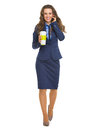 Happy business woman with cup of hot beverage talking cell phone full length portrait Stock Photos