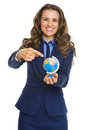 Happy business woman pointing on earth globe isolated white Royalty Free Stock Images
